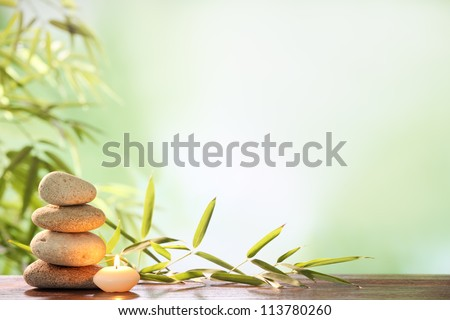 Spa still life with stacked of stone,burning candle and bamboo leaf