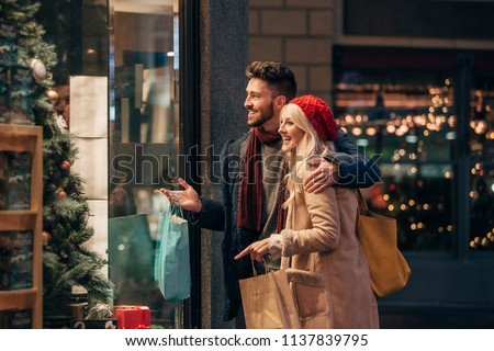 Side view of a couple doing some window shopping at christmas. The mid adult male has his arm around the mid adult female and they are talking about wats in the window. #1137839795