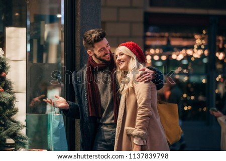 Side view of a couple looking through a store window while christmas shopping together. #1137839798