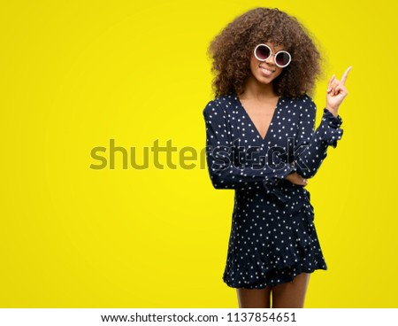 African american woman with sunglasses and summer dress very happy pointing with hand and finger to the side #1137854651