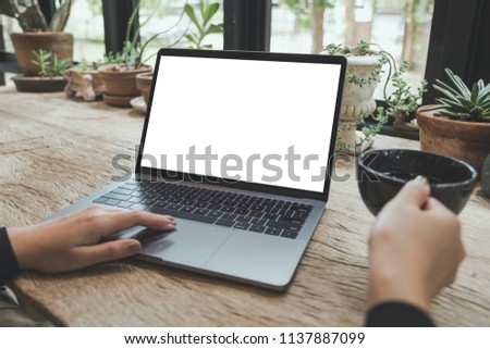 Mockup image of woman using and typing on laptop with blank white desktop screen while drinking coffee on vintage wooden table in cafe #1137887099
