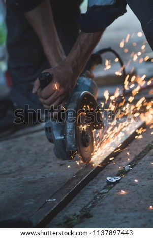 Cutting metal with grinding machine causing spark #1137897443