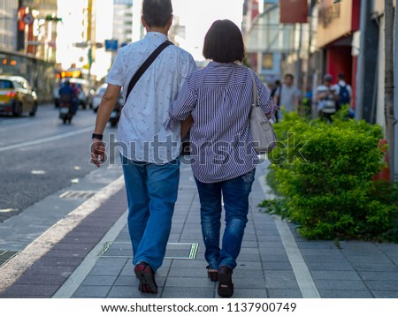 Woman and man holding hands walking #1137900749