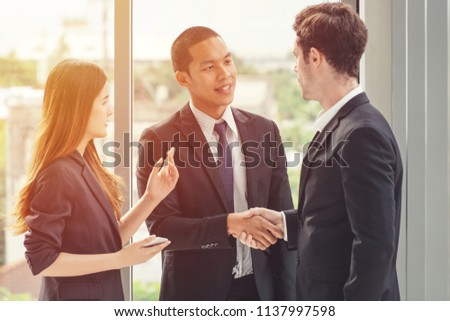 Two businessmen shaking hands with a woman secretary/translator standing on the side.