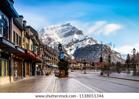 View of a busy street at Banff city Canada during transition season from winter to snow #1138051346