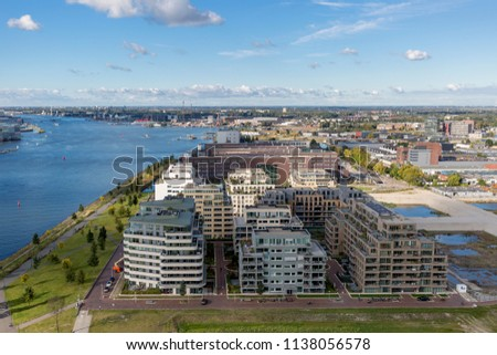 Modern architecture in the port area of Amsterdam, The Netherlands, seen from a high vantage point against a blue sky with clouds #1138056578
