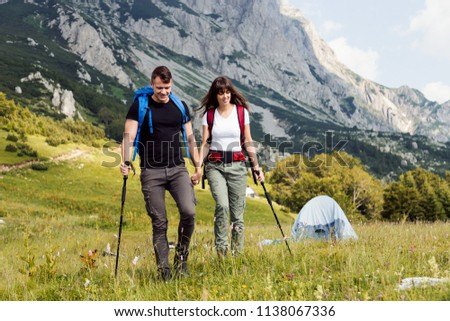 Young couple with backpack walking at mountain #1138067336