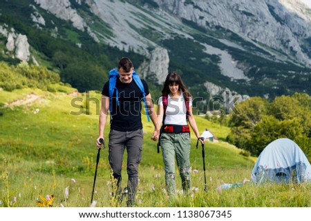 Young couple with backpack walking at mountain #1138067345