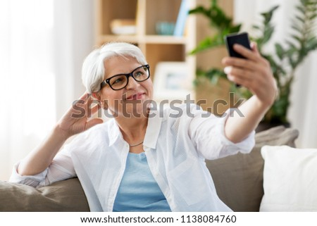 technology, communication and people concept - happy senior woman taking selfie by smartphone at home #1138084760
