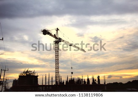 Crane lift is a large crane. Used for lifting equipment for building high-rise buildings behind the sky after the rain is very beautiful. The electric poles are straight lines along the road. #1138119806