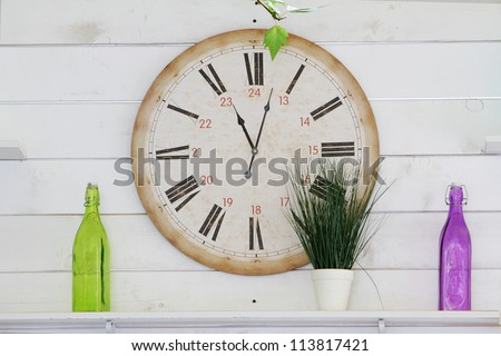 white wooden wall decorated with clocks and glass bottles