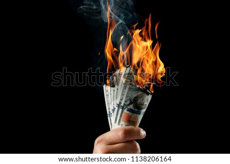 Male hand close-up, holds burning money in hands, burning US dollars. Black background, isolate. The concept of inflation, a decrease in the purchase of foreign currency, and devolution. Royalty-Free Stock Photo #1138206164