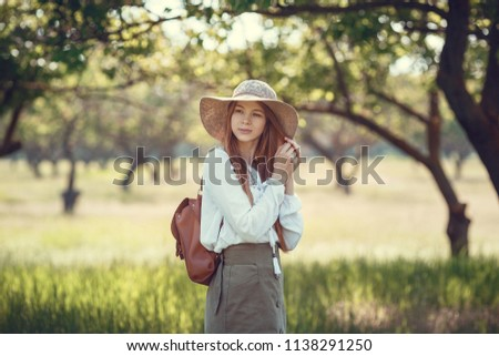 young girl in a straw hat travels green meadows. Beautiful red-haired hipster woman in a green garden #1138291250