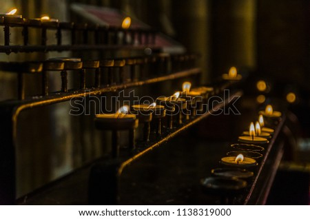 Candelabra with candles lit and half-extinguished that are offerings left by the religious faithful. #1138319000