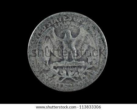 Close-up photograph of the eagle side of a 1942 United States silver quarter on a black background.  The coin is very worn down and scratched. #113833306