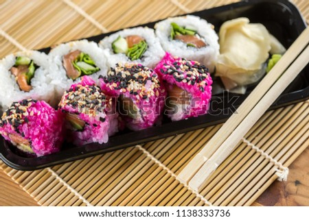 Japanese salmon sushi mix Bento with inside out rolls with avocado, cucumber and rocket salad in take away plastic tray #1138333736