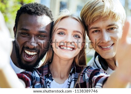 One more shot. Portrait of multicultural friends smiling while spending their day together and posing for a selfie outdoors. #1138389746