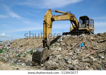 Backhoe at garbage dump with blue sky. #113843077