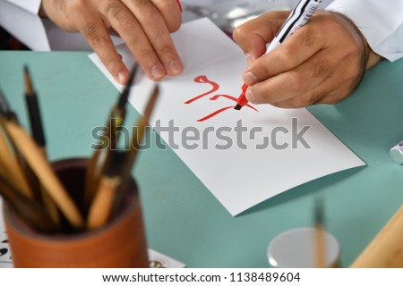 Hands of a man writing red arabic letters on a white sheet of paper. Four arabic letters mean M. A. R. A. in english alphabet. Decorative handwriting. Calligraphy. Selective focus on letter