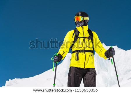 Skier standing on a slope. Man in a light suit, the helmet and mask in skiing is to ski. In the background snow-capped mountains , skiers . Caucasus Mountains, Elbrus, Russia #1138638356