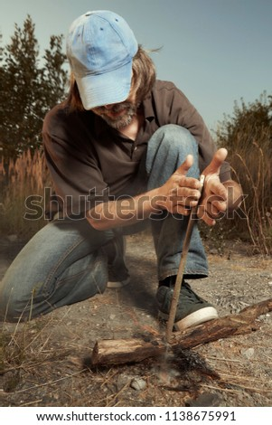 Man in hat successfully made a fire with wood stick friction #1138675991