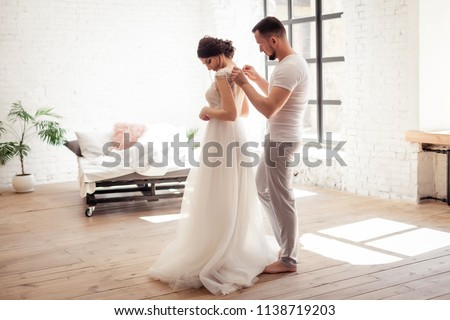 the bride dresses the dress with her husband #1138719203