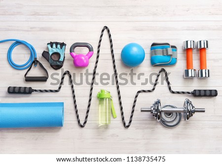 Sports equipment on a white wooden background. Top view. Motivation #1138735475