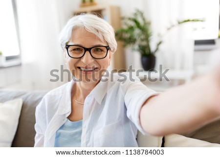 technology, communication and people concept - happy smiling senior woman in glasses taking selfie at home #1138784003