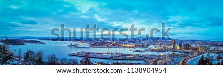Beautiful panoramic aerial view of the fiords, cloudy sky, trees and plants, and buildings of the city of Oslo, in Winter, in Norway, Scandinavia. The picture was taken from a mountain near the city.