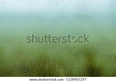 Dirty glass with drops of rain. Raindrops on green and blue clear background. Greenery and sky in bokeh outside window. Droplets and stains close up. Detailed transparent texture in macro.