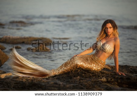 Beautiful fashionable mermaid sitting on a rock by the sea #1138909379