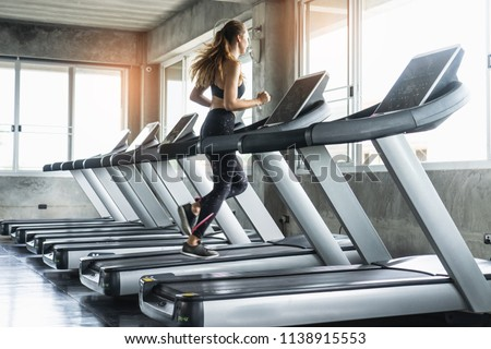 Cute young woman exercising on  treadmill at a gym.Active young woman running on treadmill. smile and funny emotion. #1138915553