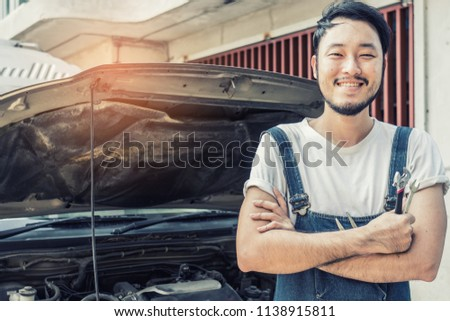 Fixing car engine in automobile repair garage. Handsome mechanics in uniform are repairing car while working in auto service #1138915811