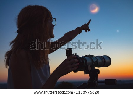 Girl looking at lunar eclipse through a telescope. My astronomy work. Royalty-Free Stock Photo #1138976828