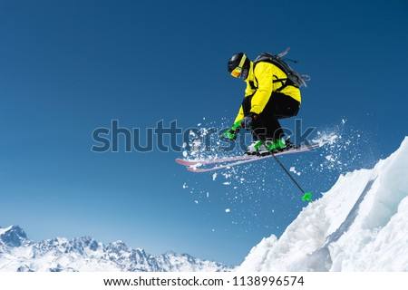 A skier in full sports equipment jumps into the precipice from the top of the glacier against the background of the blue sky and the Caucasian snow-capped mountains. Elbrus region. Russia #1138996574