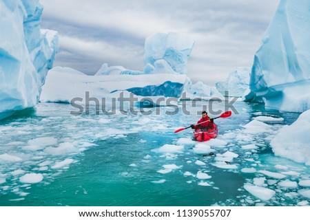 extreme tourism, winter kayaking in Antarctica, adventurous man paddling on sea kayak between icebergs #1139055707