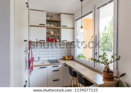 White tiny modern kitchen with red components, reconstruction, cosy small panel house in Prague, Czech Republic #1139077133
