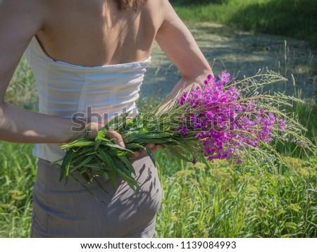 Bouquet of flowers of Ivan-tea in the hands of the girl behind her. #1139084993