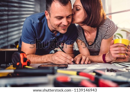 Wife kissing husband during kitchen renovation while they looking at blueprints