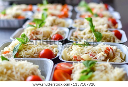 preparation of dietary dishes in the kitchen for the delivery of dietary lunch, basil, tomato cherry, cheese, pasta and chicken fillet. concept of takeaway food. selective focus #1139187920