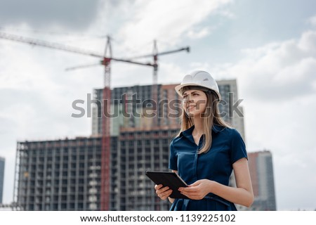 Female construction engineer. Architect with a tablet computer at a construction site. Young Woman looking, building site place on background. Construction concept #1139225102