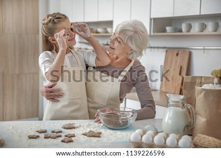 Cheerful girl is having fun with her granny in kitchen. She is holding self-made cookies near eyes and smiling. Old woman is embracing her with joy #1139226596