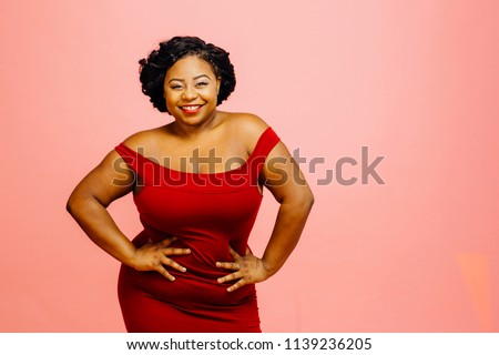Portrait of a happy and confident plus size model in red dress, smiling  #1139236205