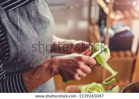 Woman standing by the old wooden table and peeling apples #1139265047