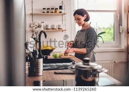 Woman wearing grey apron standing in the kitchen and cutting apples #1139265260