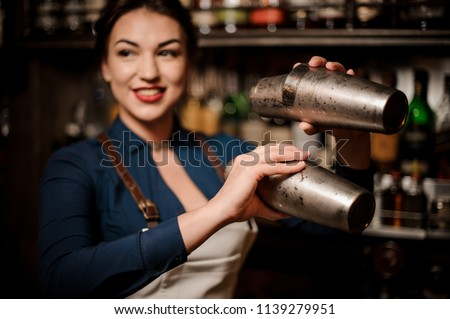 Attractive bartender girl in the white apron holding in her hands two steel cocktail shakers at the bar counter #1139279951