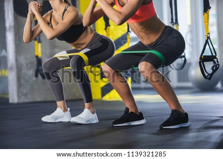 Close up of athletic women in squat together in gym. Couple of fit girls are exercising with resistance band for lower body relief. They are wearing sport clothes and sneakers #1139321285