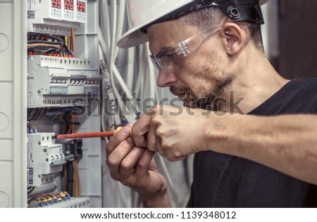 a male electrician works in a switchboard with an electrical connecting cable, connects the equipment with tools, the concept of complex work, space for text #1139348012