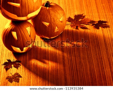 Picture of halloween glowing pumpkins border, three orange carved pumpkins and old dry leaves on wooden background, scary holiday shadow, traditional halloween decoration, jack-o-lantern #113935384