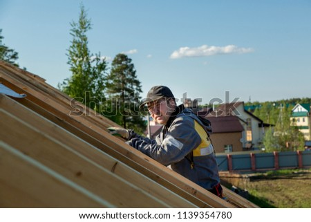 The builder stands on the roof of a wooden house and thinks how to put transverse lags #1139354780
